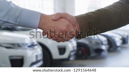 Close up of dealer and new owner handshake after concluding a car deal in auto show or salon. Concept of car dealerships, used cars, car sale and rent, auto deal