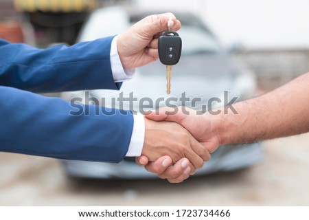 Close up of dealer giving key to new owner and shaking hands in auto show.auto business, car sale, deal,concept