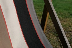 Close up of deckchair on grass showing fabric and wooden frame