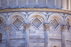 Close up of decorated facade of Leaning Tower of Pisa. Marble mosaics, sculpt columns and ornate arches. Architectural details. Medieval european art architecture. Famous Facade of the building. Italy