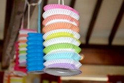 close up of decorative rainbow coloured paper lanterns hanging with string from an indoor ceiling.  A concertina ornament of many colours