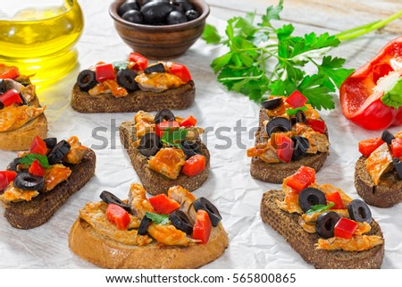 close-up of delicious bruschetta with pieces of mackerel fish, rings of black olives, red bell pepper on white plate on paper, bottle with cooking oil and parsley on background, top view