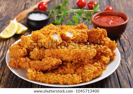 close-up of delicious crispy fried chicken breast strips on white plate, on old rustic  wooden table with tomato sauce and lemon slices, easy recipe for outdoor picnic or party, view from above