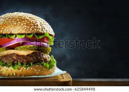 Close-up of delicious fresh home made burger with lettuce, cheese, onion and tomato on a rustic wooden plank on a dark background