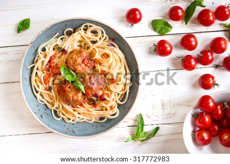 Close-up of delicious spaghetti with meatballs and tomato sauce on a plate. Serving on a white rustic wooden table. An Italian-American dish. Top view. Selective focus
