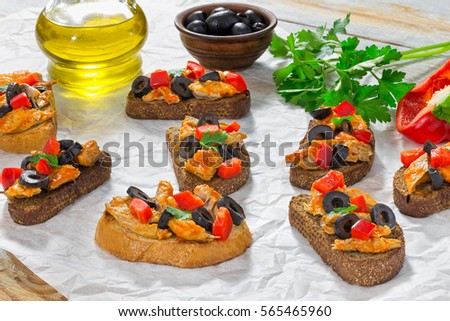 close-up of delicious tapas with pieces of mackerel fish, rings of black olives, red bell pepper on white plate on paper, bottle with cooking oil and parsley on wooden background, top view