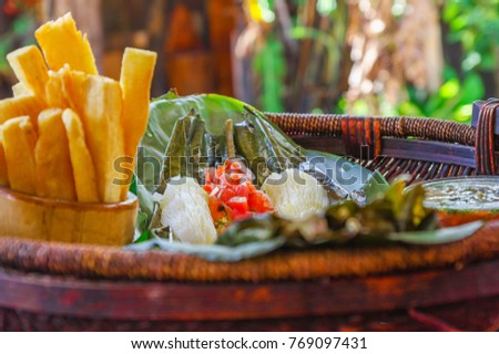 Shutterstock Close up of delicious typical amazonian food, fish cooked in a leaf with yucca and plantain, bowl of salad and fried yucca, served in a wooden platen over a wooden table