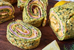 close-up of delicious zucchini roulade with melted cheese and boiled ham, cut in slices on a cutting board with savory yogurt sauce and ingredients on a white table, view from above