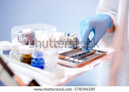 Close up of dentist's hands picking up dental equipment. Zdjęcia stock ©