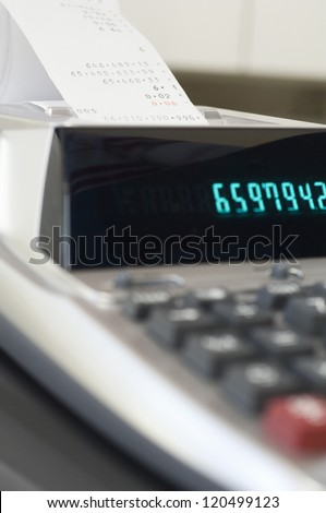 Close up of desktop calculator printing out expenditure receipt