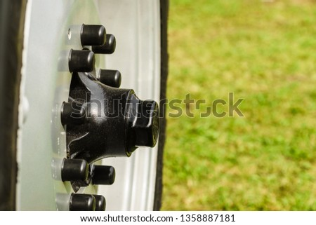 Close up of detailed black bolts screws on car truck wheel. Abstract industrial details concept.
