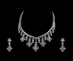 Close up of diamond necklace on black background with diamond ear ring