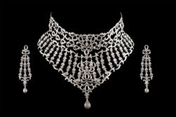 Close up of diamond necklace on black background with diamond earrings.