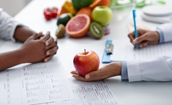 Close up of dietologist and patient female hands over doctor workplace, nutritionist holding apple