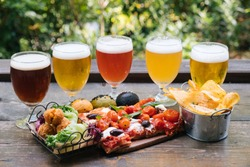 close up of 5 different beer glass  with mix finger food on a wood table and plants background, outdoor natural light, aperitif, happy hour