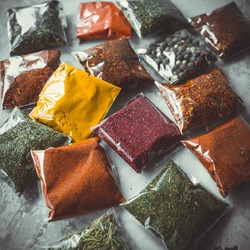 Close-up of different types of assorted spices in transparent bags