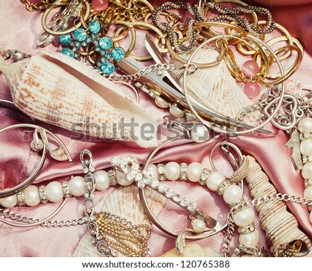 Close up of different women accessories and jewelery on pink fabric
