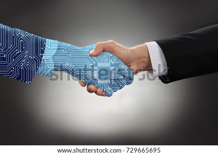 Close-up Of Digital Generated Human Hand And Business Man Shaking Hands Against Grey Background Stock photo ©