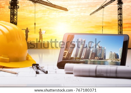 Close-up Of Digital Tablet And Hardhat On Blueprint In Front Of Construction Site