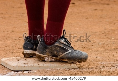 Close up of dirty baseball cleats standing on base with dark red socks