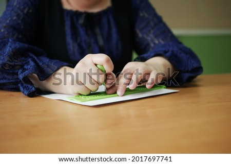 Close-up of disability blind person woman hands writing braille text on paper by using slate and stylus tools making embossed printing for Braille character encoding.  Stock foto ©