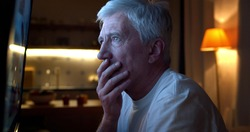 Close up of disappointed aged man watching tv news sitting near screen. Side view of retired male watching football match on tv and feeling unhappy late in evening