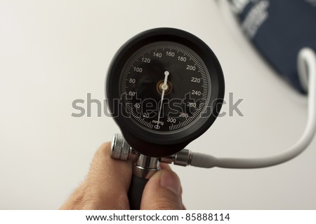 Close up of display of sphygmomanometer, held by male hand