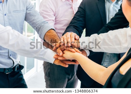 Close-up of diverse business people of men and woman putting hands together - collaboration and togetherness in work office concept