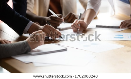Close up of diverse businesspeople gather at office desk discuss company financial paperwork at meeting together, multiracial colleagues brainstorm work with documents at briefing in boardroom