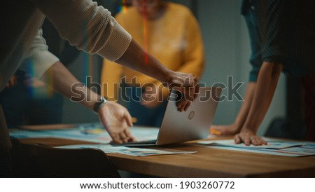 Close Up of Diverse Multiethnic Team Having Conversation in Meeting Room in a Creative Office. Colleagues Lean On a Conference Table, Look at Laptop Computer and Make Notes with Pencils on Notebooks. Foto stock ©