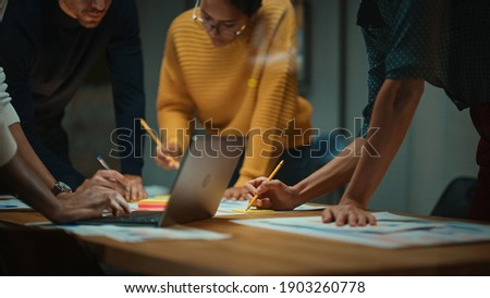 Close Up of Diverse Multiethnic Team Having Conversation in Meeting Room in a Creative Office. Colleagues Lean On a Conference Table, Look at Laptop Computer and Make Notes with Pencils on Notebooks.