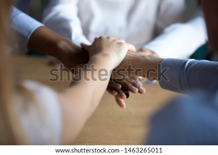 Close up of diverse people join stack hands motivated for shared success and goal achievement, multiracial colleagues engaged in teambuilding show support, unity and team spirit. Teamwork concept