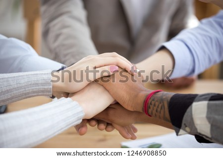 Close up of diverse people put hands together in stack showing mutual support and help, multiethnic students or workers involved in teambuilding activity at workplace, team collaborate being one