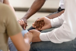 Close up of diverse religious people sit in circle hold hands pray together hope for help, multiracial men and women group gathering express support and understanding at psychological therapy session