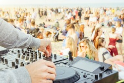 Close up of DJ's hand playing music at turntable at beach party festival - Crowd people dancing and having fun in club outdoor - Concept of youth summer party lifestyle