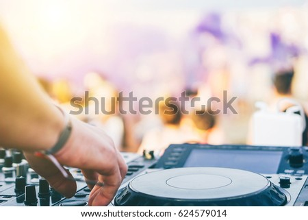 Close up of DJ's hand playing music at turntable on a beach party festival - Portrait of DJ mixer audio in a beach club above the crowd dancing and having fun - Party, summer, music and people concept