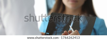Close-up of doctor hands holding skiagram. Surgeon talking about wrist trauma. Smiling intern listening carefully to traumatologist. Traumatology and health care concept Stock photo ©