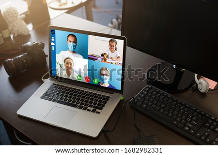 Close-up Of Doctor Having Video Conference On Laptop At Wooden Desk