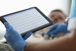 Close-up of doctor holding tablet with graphic. Modern medicine and technology. Medical worker in protective gloves. Ecg and cardiology appointment concept