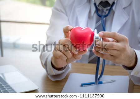 Close up of doctor with stethoscope examining red heart,Health concept #1111137500