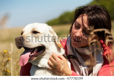 Close-up of dog with tongue hanging out and woman embracing its