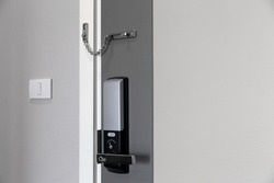 Close up of Door security latch chrome metal chain and digital door lock on modern wooden door for protection and safety home. copy space