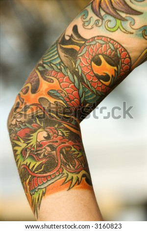 stock photo : Close up of dragon tattoo on arm of Caucasian woman.