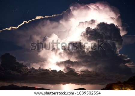 Close-up of dramatic thunderstorm with huge clouds and lightning over islands in the sea at night.