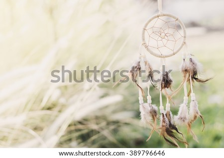 Close up of Dream Catcher on meadow background with soft vintage tone #389796646