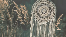 Close up of dream catcher on meadow background with soft vintage tone. Hand made. Background for website design. Photo on the topic hygge, fika and lagom.