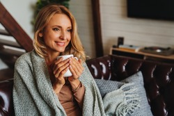 Close up of dreaming middle aged woman sitting in living room with cup of coffee or tea enjoying under blanket