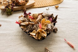 Close-up of dried flowers and herbs potpourri mix used for aromatherapy, isolated on linen background.