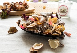Close-up of dried flowers and herbs potpourri mix used for aromatherapy on linen background.