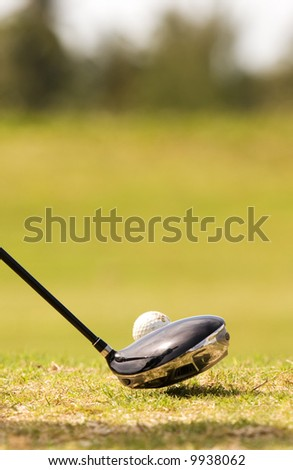close up of driver golf club, and golf ball with reflection of golfer in club